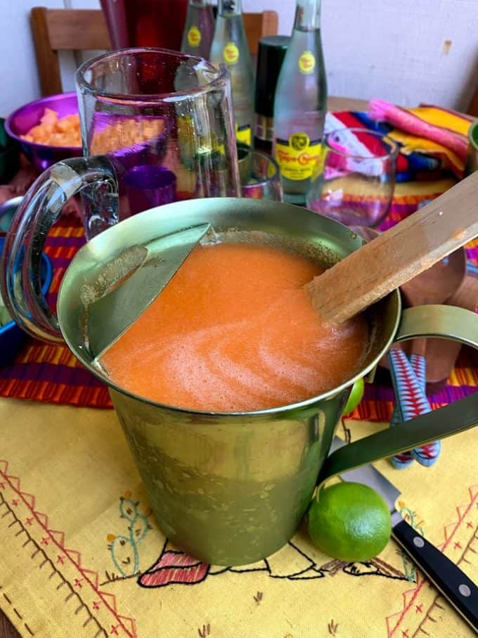 small pitcher with chilled agua fresca with wooden spoon inside