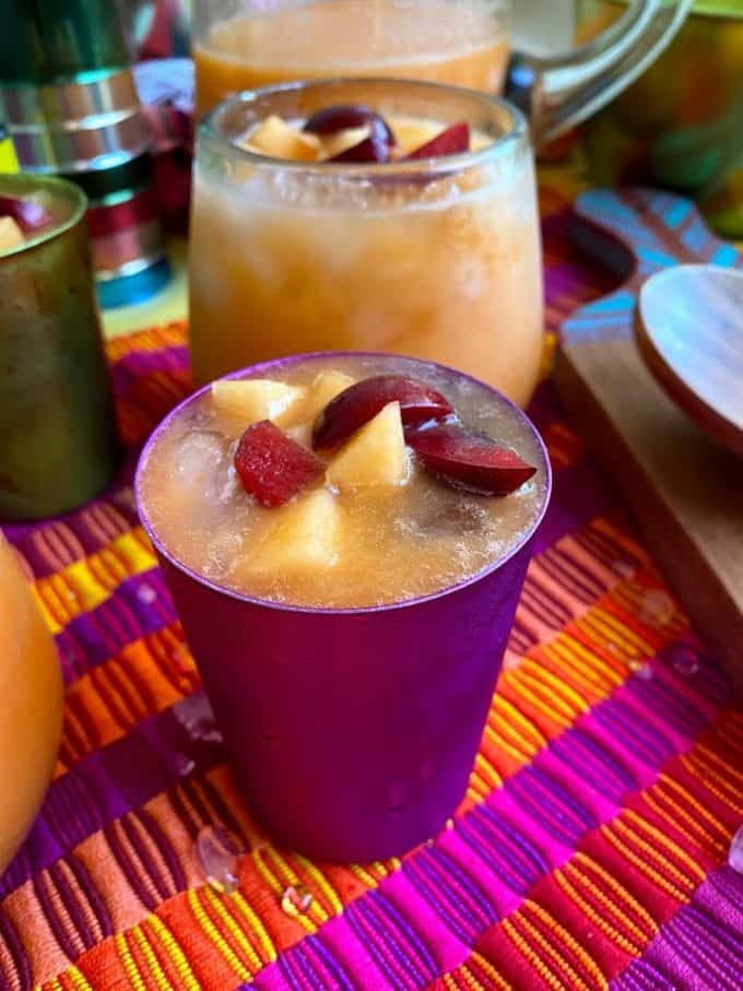 colored aluminum glass filled with melon agua fresca, garnished with fruit