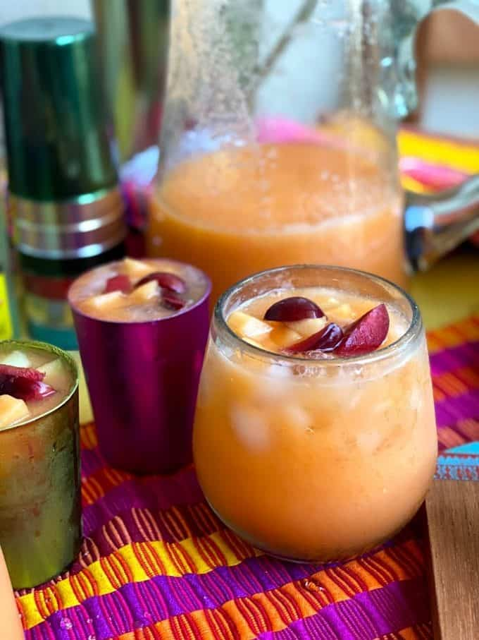 agua fresca served in a glass and in smaller aluminum cups in different colors. Pitcher in the back round