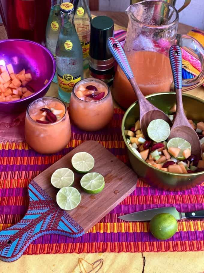 agua fresca served in glasses, cutting board with sliced limes, fruit salad in bowl with wooden serving spoons. Pitcher, extra glasses and mineral water bottles