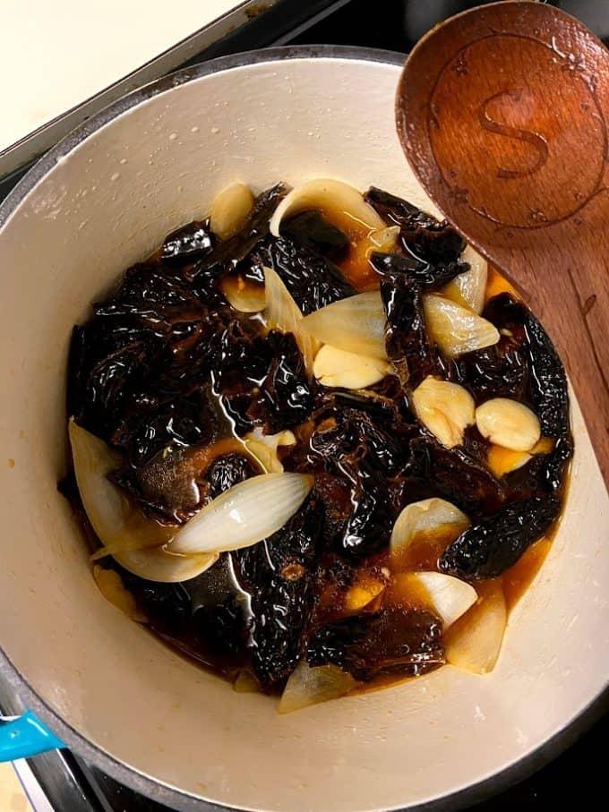 ingredients for salsa negra cooking in heavy pot