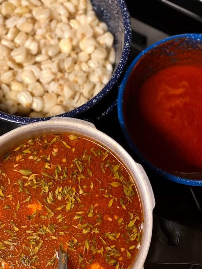 stove top view of menudo, chile sauce and maiz