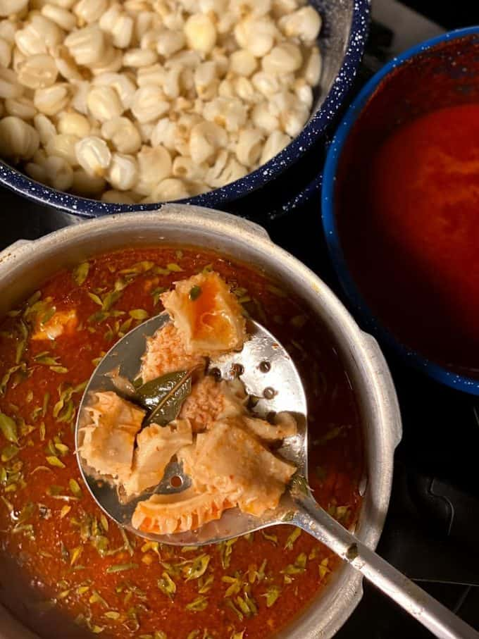 top view of stove top menudo, maiz and red chile sauce