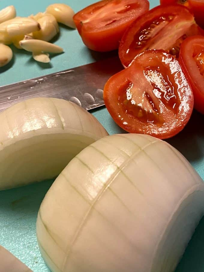tomatoes, onion and garlic on cutting board