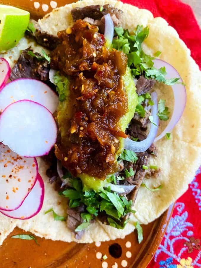 top view of steak tacos with salsa borracha garnish