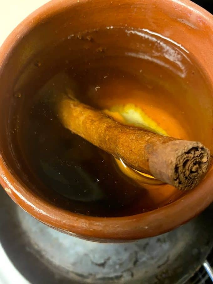 clayware pot filled with water, cinnamon stick, piloncillo and orange peel