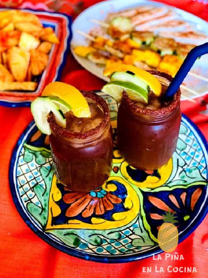 two micheladas on a mexican platter with fruit appetizers