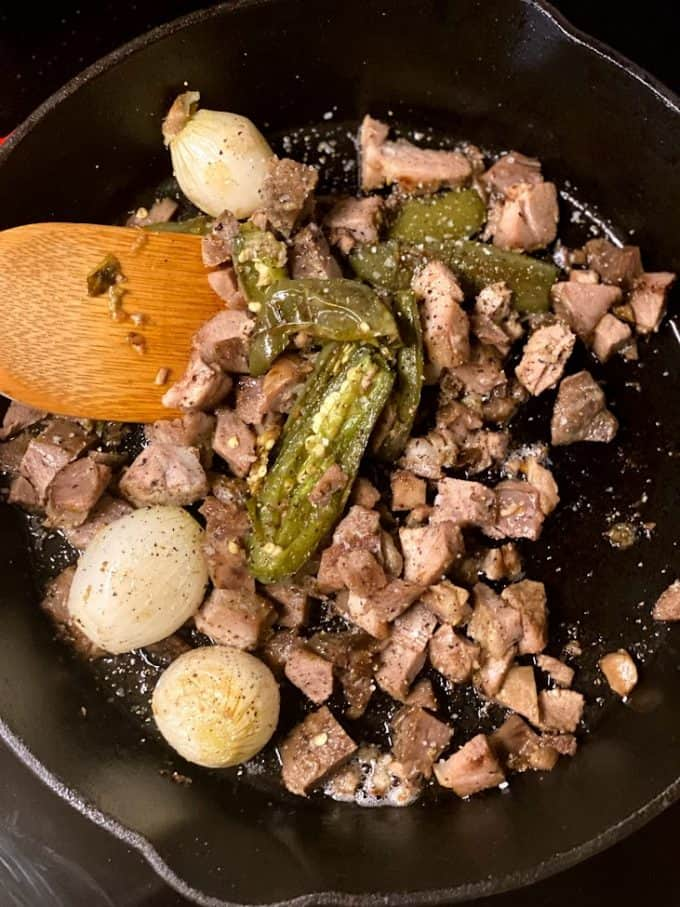 diced carnitas frying in cast iron skillet with onions and jalapeños
