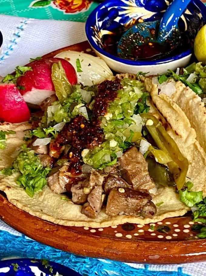 carnitas toaco with salsa cruda and salsa macha close up