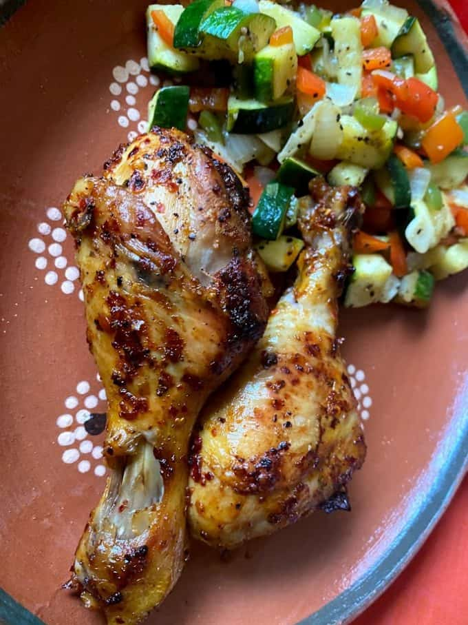 roasted drumsticks up close on plate with  vegetables saute