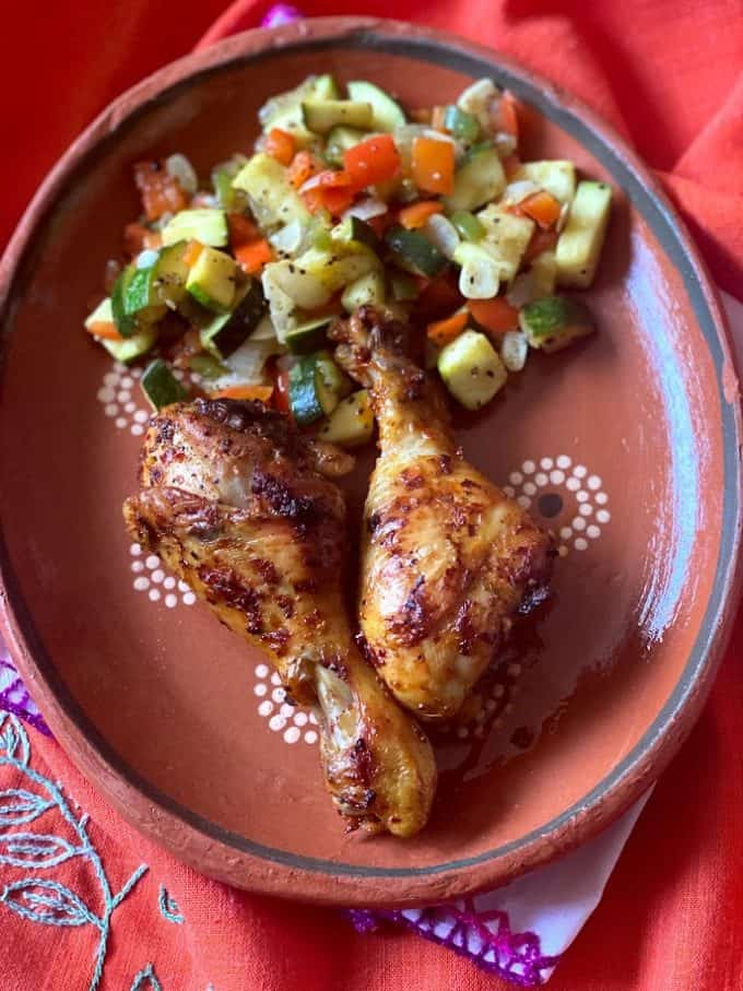 two drumsticks plated with sauted vegetables on clayware plate