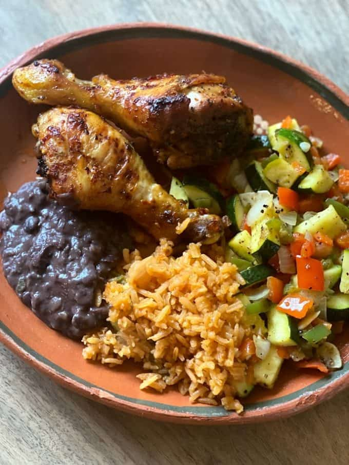 two drumsticks plated with vegetables, rice and black beans