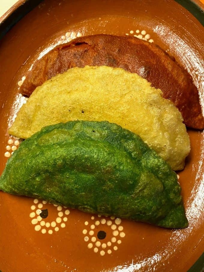 fried quesadillas or empanadas in red white and green colors on Mexican plate