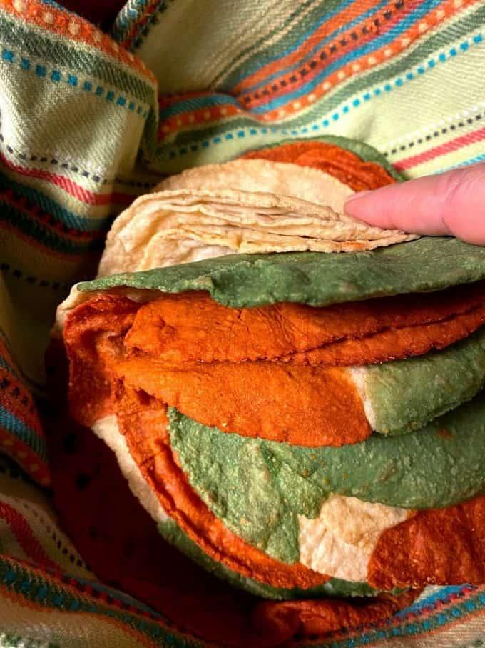 tri colored corn tortillas in tortilla warmer close up