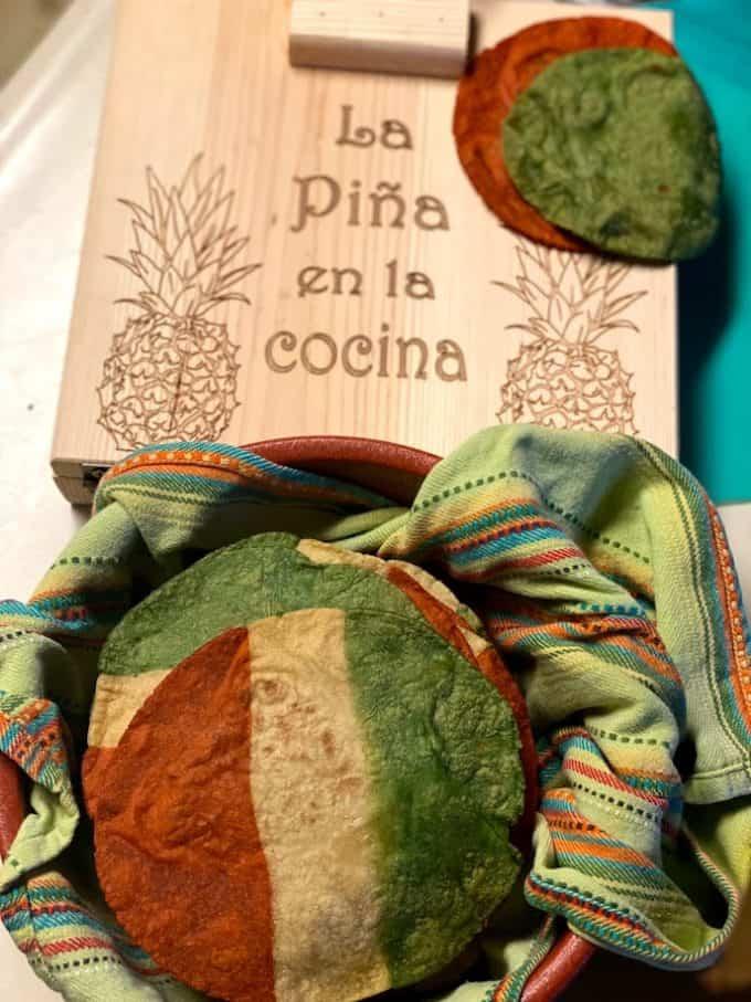 tri colored corn tortillas in tortilla warmer with wooden tortilla press