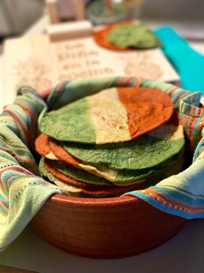 stacked tri colored corn tortillas in warmer with kitchen towel