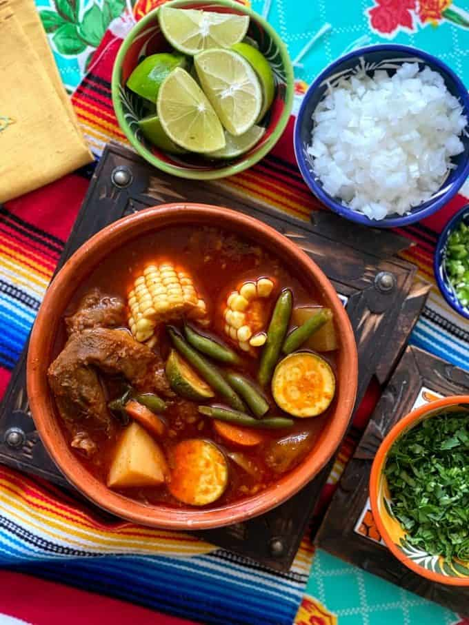 mole de olla in large bowl with fresh garnishes in smaller bowls