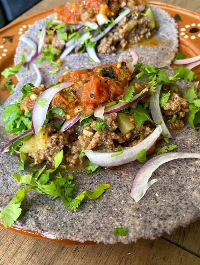 close up of picadillo taco with blue corn tortilla