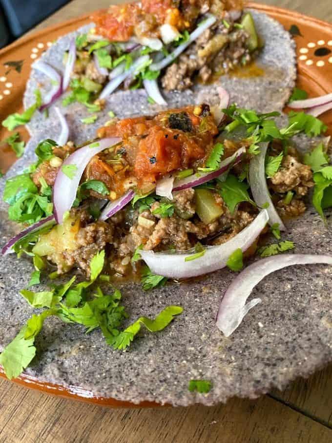 close up of beef picadillo taco on blue corn tortillas